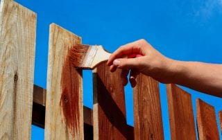 Man painting wooden fence with brown paint