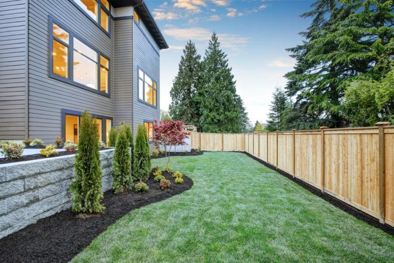 Newly landscaped home with fence surrounding it